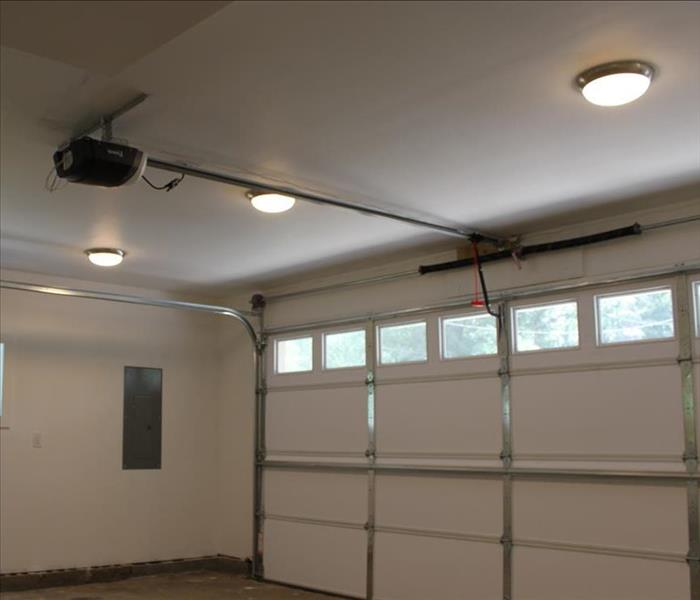 The garage has been restored thru cleaning with a new ceiling and garage door, white and bright