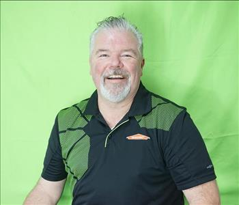 Male employee with gray hair in front of green background