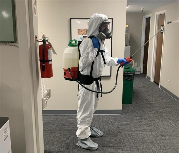 PPE suited employee fogging commercial office